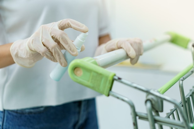 Carro de compras desinfectante de manos de mujer con spray de alcohol para el virus corona o protección covid-19.