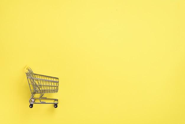 Carro de compras en fondo amarillo. estilo minimalista. tienda trolley en supermercado. venta, descuento, concepto shopaholism. tendencia de la sociedad de consumo
