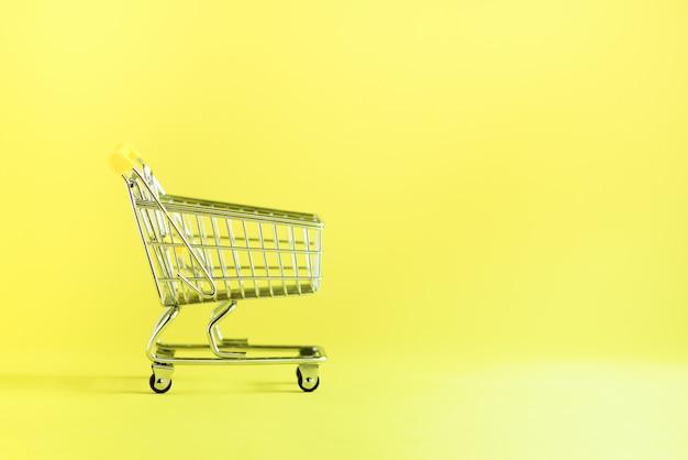 Carro de compras en fondo amarillo. tienda trolley en supermercado. venta, descuento, concepto shopaholism. tendencia de la sociedad de consumo