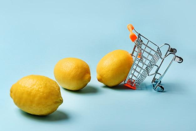 Carro de compras invertido con limones en una pared azul con un espacio de copia.