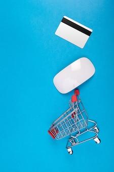 Carro de compras de juguete en la vista superior de fondo azul