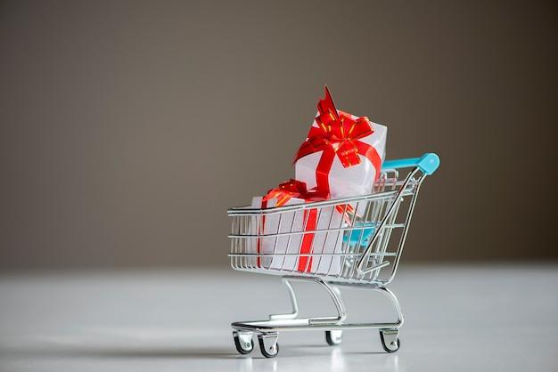 Carro de compras lleno de color blanco y rojo de cajas de regalo en superficie gris