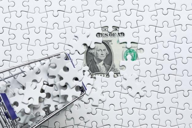Carro de compras lleno de rompecabezas sobre fondo de dinero dólar, concepto de solución empresarial, clave para el éxito