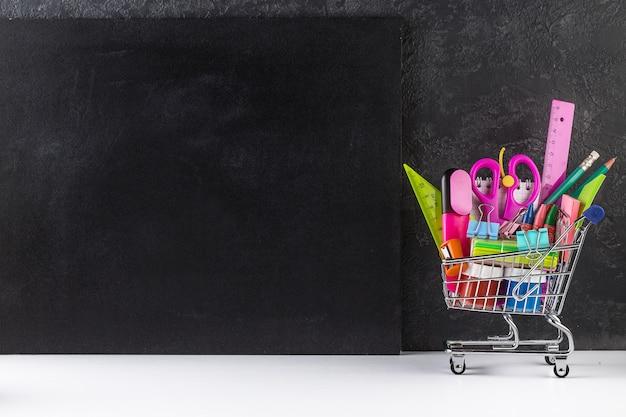 Carro de compras lleno de útiles escolares y un fondo de pizarra