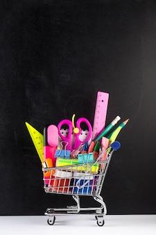 Carro de compras lleno de útiles escolares y una pizarra
