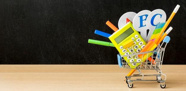 Carro de compras con lo esencial para el regreso a la escuela