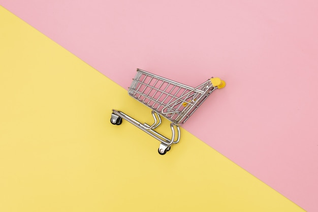 Carro de compras de metal sobre fondos rosados y amarillos.