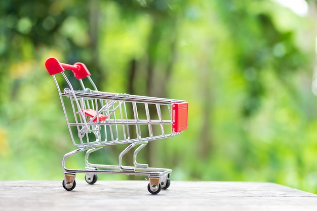 Carro de compras en miniatura en maqueta de madera sobre jardín verde borroso en la luz del mediodía