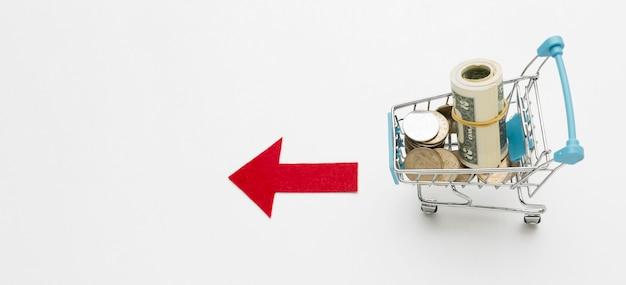 Carro de compras plano y plano lleno de dinero
