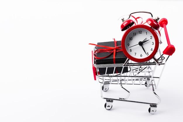 Carro de compras con regalo y despertador