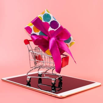 Carro de compras con regalo en la parte superior de la tableta