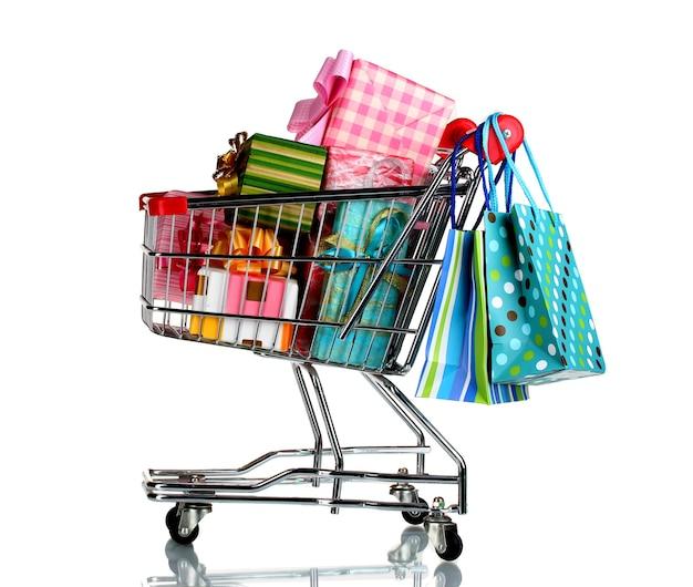 Carro de compras con regalos brillantes y bolsas de papel aislado en blanco