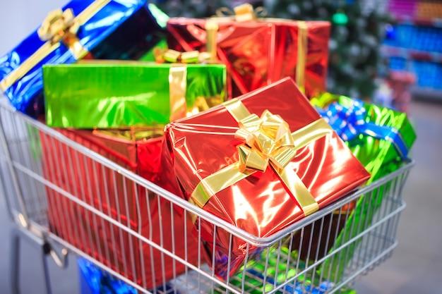 Carro de compras con regalos en el fondo del supermercado