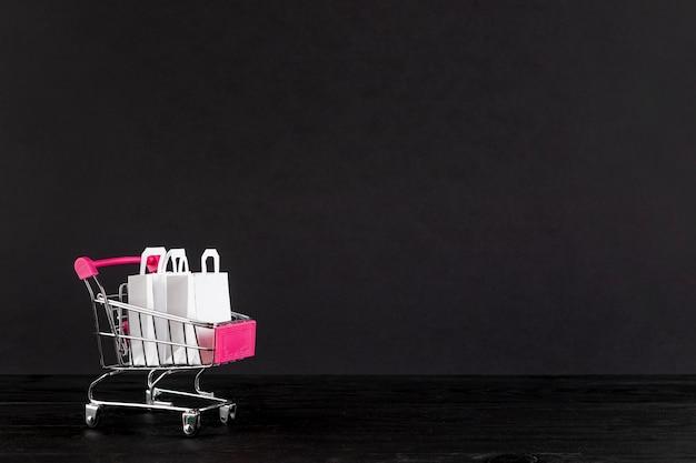 Carro de compras sobre fondo negro con espacio de copia