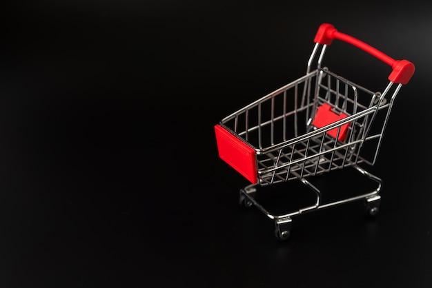 Carro de compras sobre fondo oscuro con espacio de copia