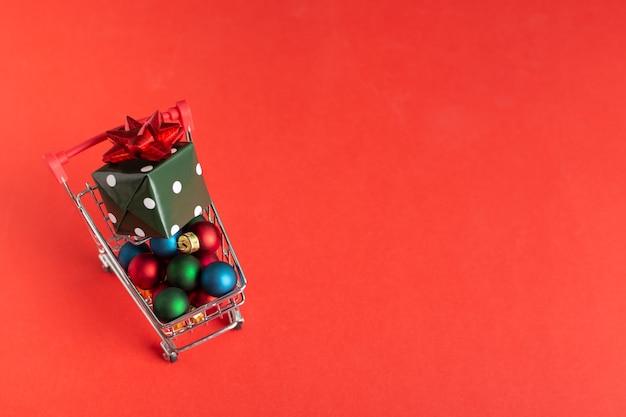 Carro de compras sobre ruedas con adornos navideños y caja de regalo sobre fondo rojo.