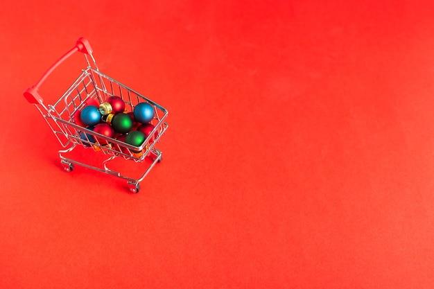 Carro de compras sobre ruedas con adornos navideños sobre fondo rojo.