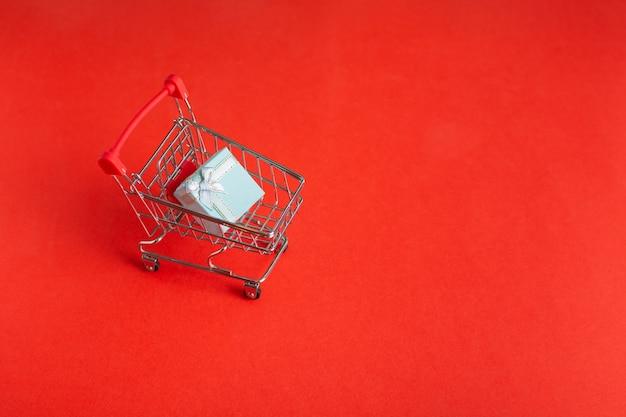 Carro de compras sobre ruedas con caja de regalo sobre fondo rojo.