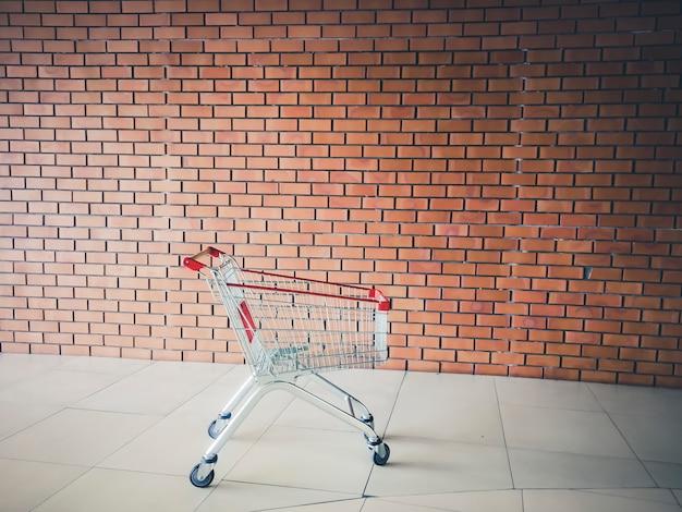 Carro de compras vacío cerca de la pared de ladrillo. carrito de supermercado. concepto de tiempo de compras
