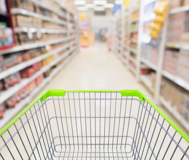 Carro de compras verde vacío con supermercado desenfoque