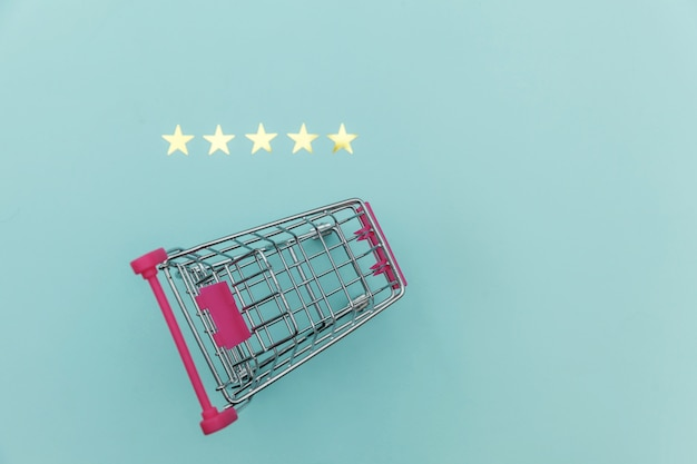 Carro de empuje de supermercado pequeño para comprar juguetes con ruedas y calificación de 5 estrellas aislado sobre fondo azul pastel. consumidor minorista que compra concepto de evaluación y revisión en línea.