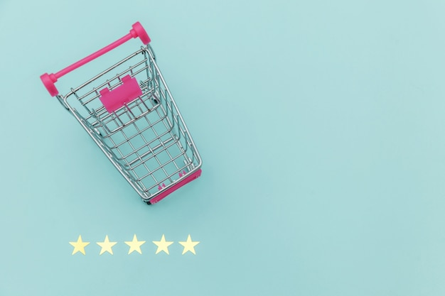 Carro de empuje de supermercado pequeño para comprar juguetes con ruedas y calificación de 5 estrellas aislado sobre fondo azul pastel. consumidor minorista que compra el concepto de evaluación y revisión en línea.