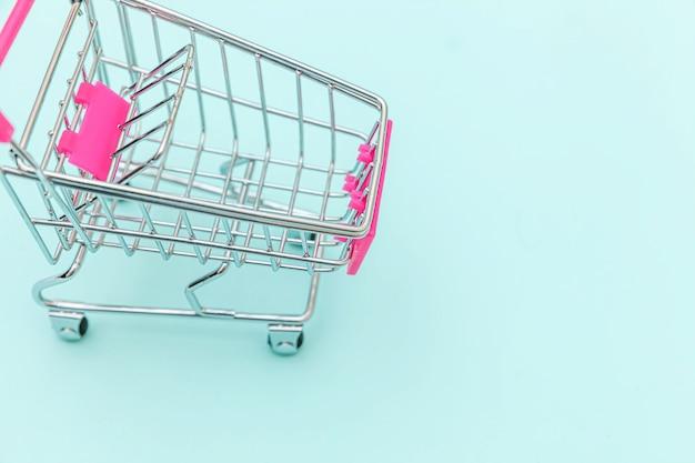 Carro de empuje de supermercado pequeño para ir de compras aislado sobre fondo azul.