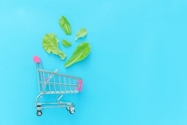 Carro de empuje de supermercado pequeño para ir de compras con hojas de lechuga verde aisladas sobre fondo azul pastel colorido