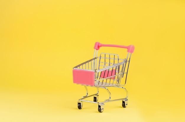 Carro de juguete de empuje de supermercado pequeño para ir de compras con ruedas sobre fondo de colores amarillo.