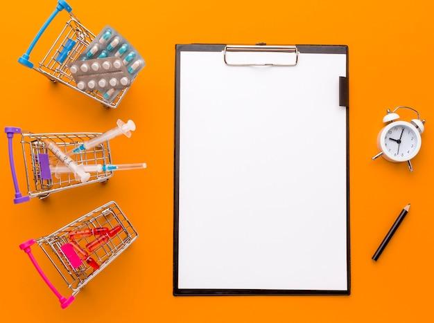 Carro de juguete con pastillas, tabletas y portapapeles