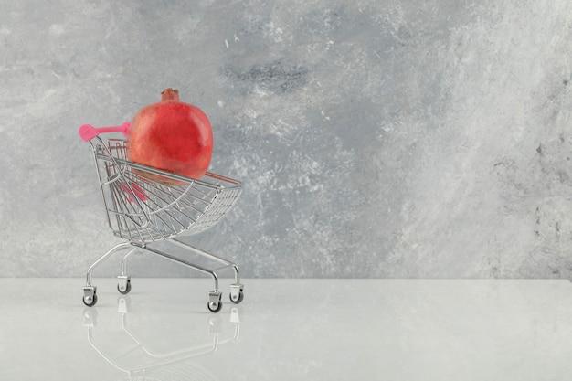 Carro pequeño con granadas rojas frescas sobre mesa blanca.