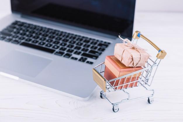 Carro pequeño de supermercado con cajas de regalo y laptop.