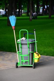 Carro de servicio de limpieza lleno de suministros y equipo junto con un contenedor de basura gris