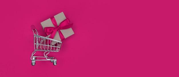 Carro de supermercado y caja de regalo sobre un fondo rosa con espacio de copia. concepto de compras.