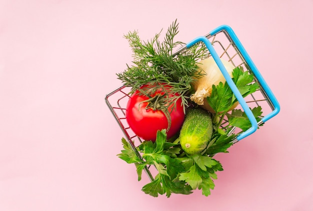 Carro de supermercado de compras de metal en rosa. concepto de canasta de alimentos. de cerca. lay flat. enfoque suave selectivo. . espacio de copia de texto.