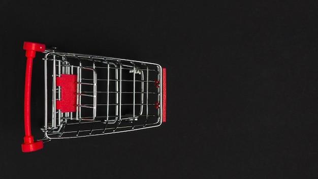 Carro de supermercado de juguete con asa roja.