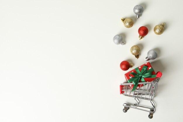 Carro de la tienda con caja de navidad y adornos en blanco