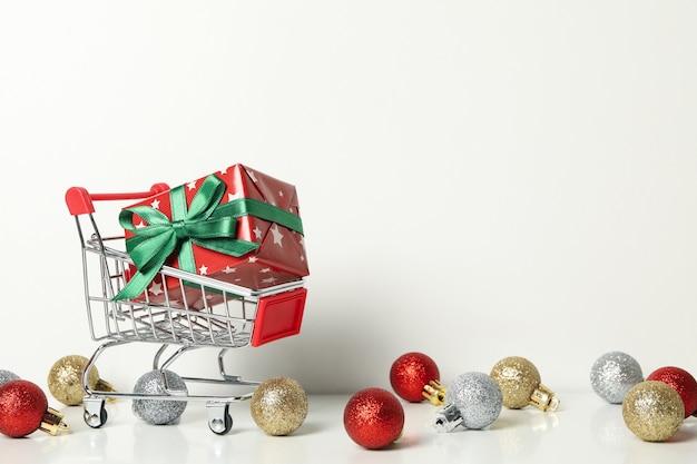 Carro de la tienda con caja de navidad y adornos sobre mesa blanca