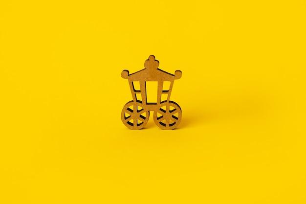 Carro vintage de madera sobre fondo amarillo, transporte vintage