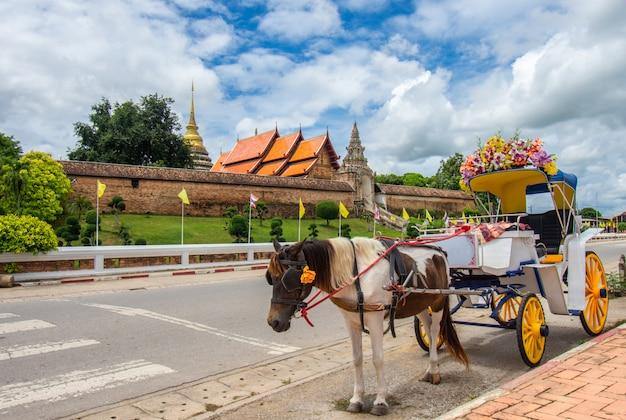 Carruaje tirado por caballos frente a wat phra that, lampang luang, tailandia para servicios turísticos