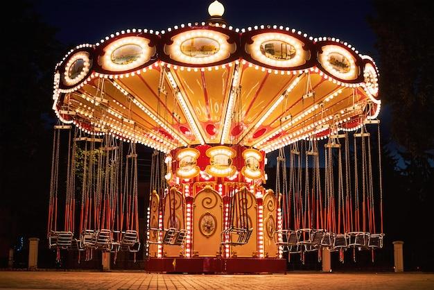 Carrusel de cadena oscilante iluminado en el parque de atracciones en la noche