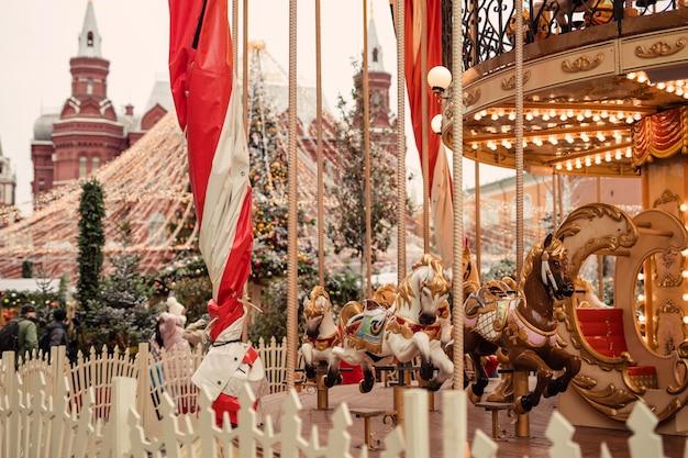Carrusel en la feria de navidad en invierno en la plaza roja de moscú