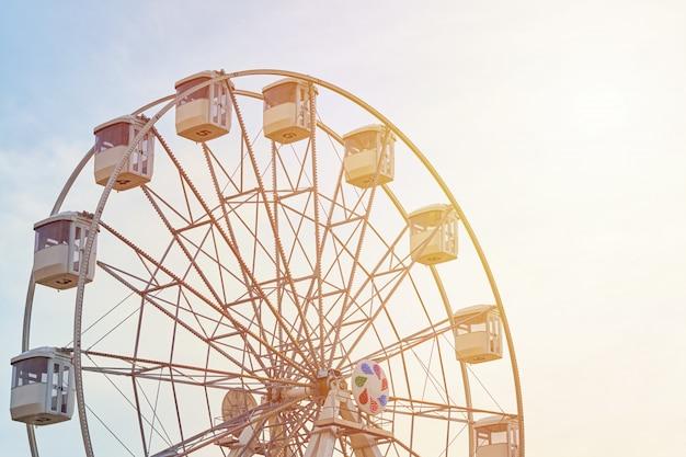 Carrusel de la rueda de la fortuna sobre el cielo con la luz del sol