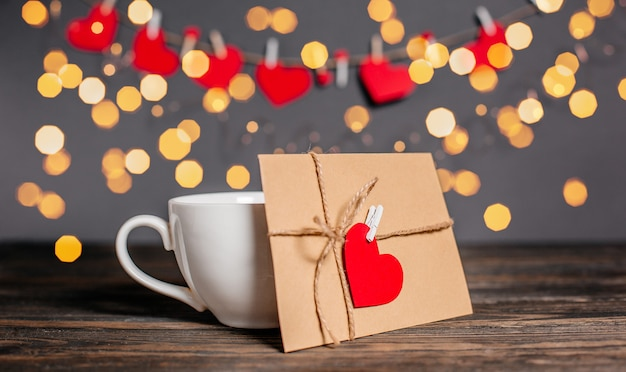 Carta de amor con un corazón junto a una taza sobre un fondo de luces, amor y concepto de san valentín en una mesa de madera