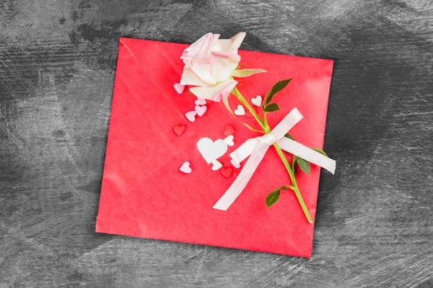 La carta de amor cuelga de una cuerda y una flor sobre un fondo oscuro. vista superior