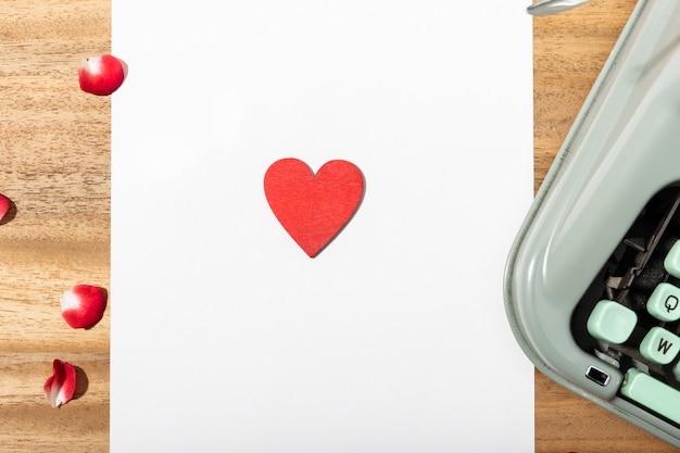 Carta de amor. escritorio con papel en blanco, máquina de escribir retro y corazón rojo
