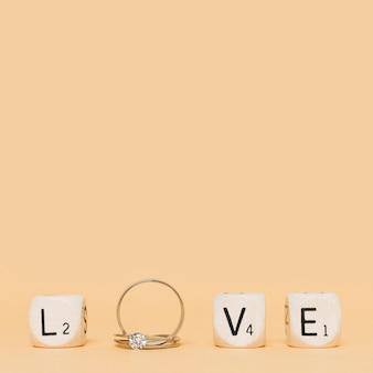 Carta de amor hecha con anillos de diamantes de boda y cubos sobre fondo crema.