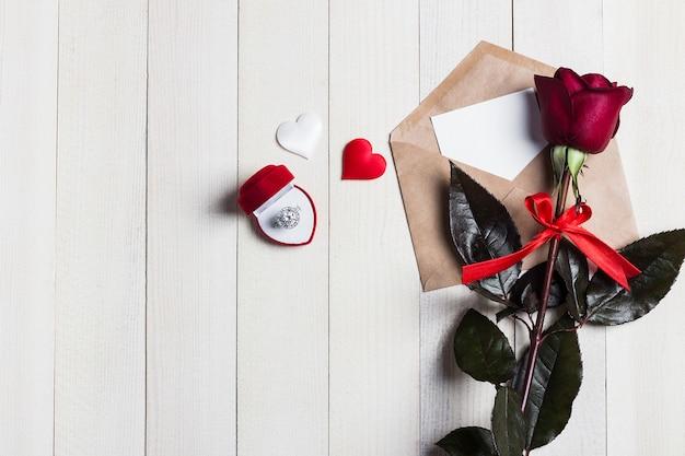 Carta de amor del sobre del día de san valentín con el anillo de compromiso de la tarjeta de felicitación en caja
