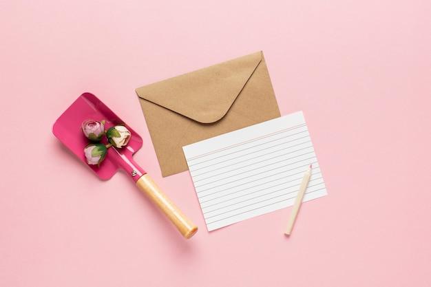 Carta blanca y pala con flores.