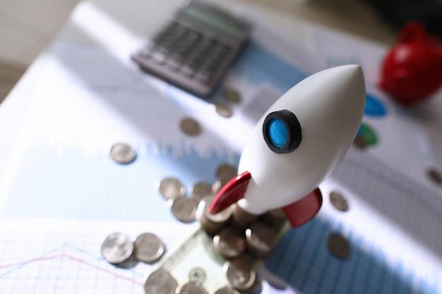En la carta de colores hay un cohete espacial de juguete y monedas sobre la mesa.